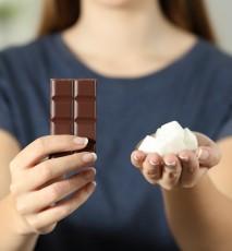 Zbliżenie na dłonie kobiety. W jednej dłoni trzyma kostki cukru, w drugiej czekoladę.