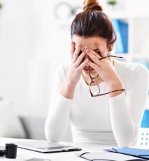 Zmęczona, młoda kobieta siedzi przy biurku. Kobieta trzyma się za głowę.