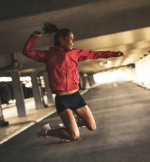 Radosna, zadowolona, młoda kobieta w trakcie treningu. Kobieta podskakuje energicznie.