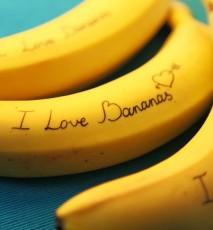 Zbliżenie na świeże banany, na bananach jest napis I love bananas.