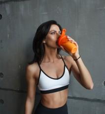 Młoda kobieta w stroju sportowym pije odżywkę białkową, białko w proszku.