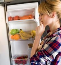 Młoda kobieta w koszuli w kratę stoi przed otwartą lodówką.