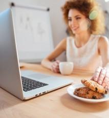 Jedzenie pod wpływem emocji. Kobieta je ciasteczka przed komputerem, w biurze.