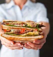 Chleb na diecie odchudzającej czy dieta bez chleba? Kobieta trzyma w dłoni dużą kanapkę.