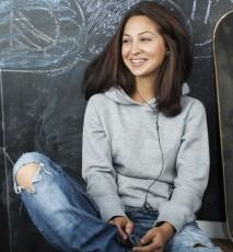 Nastolatka siedzi w klasie. Obok trzyma deskorolkę, w tle tablica szkolna. Dieta dla nastolatków