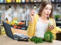 Kobieta siedząca przy blacie w kuchni, pijąca zielone smoothie.