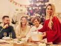 Kolacja wigilijna. Przy stole siedzą 3 osoby. Kobieta w czerwonym swetrze stoi i trzyma wazę z zupą. W tle choinka.