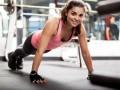 Kobieta na siłowni, uśmiechnięta robi pompki
