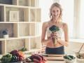 Kobieta w krótkim topie, z płaskim, zgranym brzuchem w kuchni. Obok warzywa. Kobieta trzyma w dłoni brokuł.