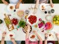 Widok od góry na stół piknikowy. Na stole owoce, ciasta, napoje. Widoczne także wyciągnięte ręce.