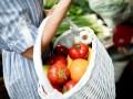 Zbliżenie na dłoń, która trzyma biały, wiklinowy koszyk ze świeżymi warzywami.
