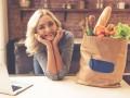 Młoda kobieta w kuchni. Obok torba papierowa z zakupami spożywczymi