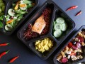 Na szarym tle leżą plastikowe opakowania z cateringu dietetycznego. W środku jest łosoś z warzywami.